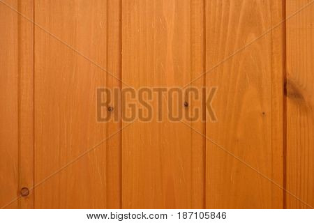 Vertical wall paneling, made from dark orange natural wood with several small scratches.  Retro background. Wooden texture.