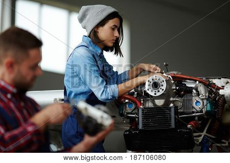 Side view portrait of modern woman repairing engine parts in workshop with man beside, both wearing workers uniform and overalls