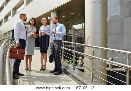 Group of young successful business people talking, discussing work outside modern office building