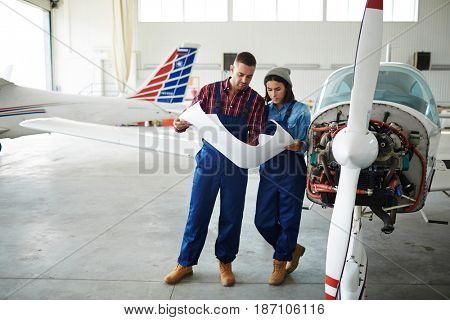 Two modern aircraft engineers, man and woman, reading construction plans standing by disassembled jet plane in hangar