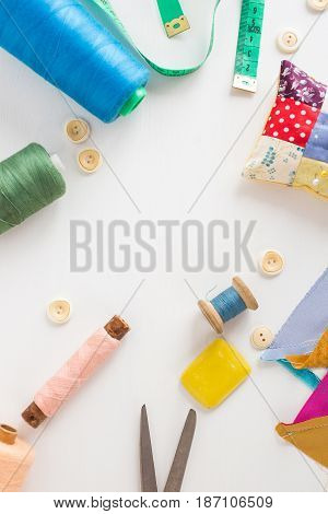 sewing tools, patchwork, tailoring and fashion concept - closeup on white desk, colorful thread spools, measuring meter, buttons, scissors, pincushion, equipment for needlework, vertical, flat lay