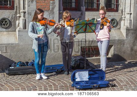 Bruges Belgium - 11 April 2017 - Three female teen violinists play for donation on a street of Bruges Belgium on April 11 2017