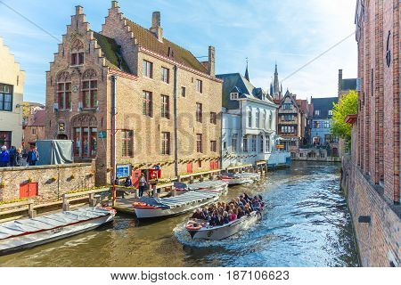 Bruges Belgium - 11 April 2017 - Tourists enjoy their river around city tour on small tour boat on river of Bruges Belgium on April 11 2017