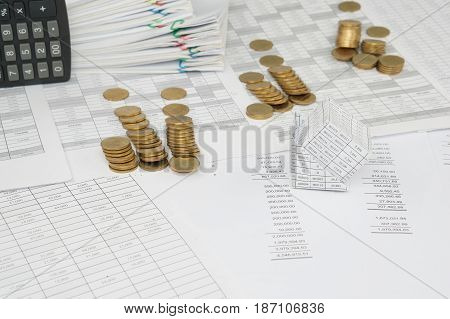 Bankruptcy of house and pile of gold coins overthrow on finance account have blur calculator place vertical and overload of paperwork with colorful paperclip as background. poster