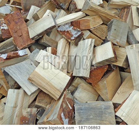 Heap of split firewood. Natural country background. Wood and lumber texture, rural wallpaper.