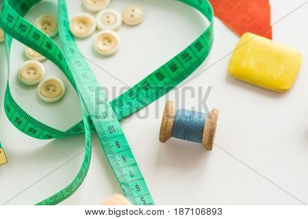 needlework, craft, sewing and tailoring concept - macro with white clothing buttons, cute green measuring meter, blue thread in the bobbin and soap for cutting on white background, top view, flat lay