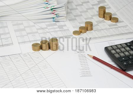 Brown Pencil And Calculator On Balance Sheet With Gold Coins