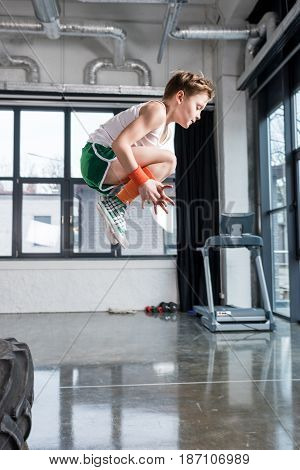 side view of kid boy jumping at fitness studio children sport concept
