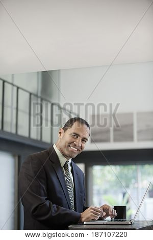 Mixed race businessman using laptop