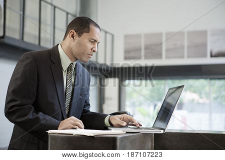 Mixed race businessman typing on laptop