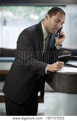 Mixed race businessman talking on telephone