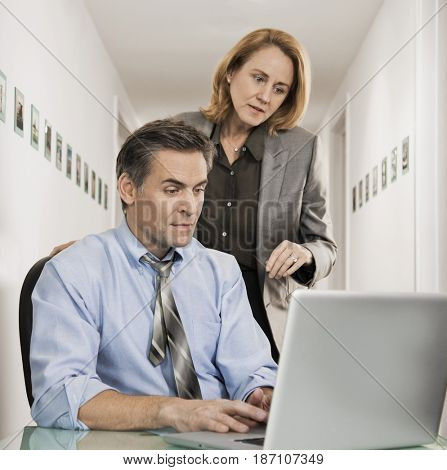 Caucasian co-workers looking at laptop