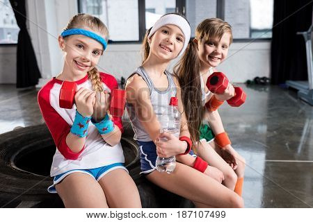 Adorable Kids In Sportswear Sitting On Tire At Fitness Studio, Children Sport Concept