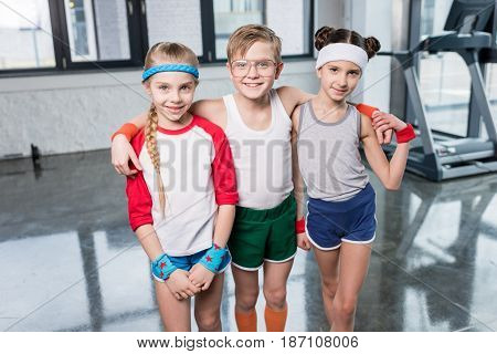 Adorable Little Children In Sportswear Standing Embracing And Smiling At Camera In Gym, Children Spo