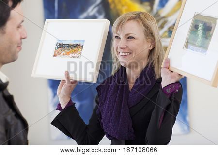 Caucasian woman showing paintings to customer