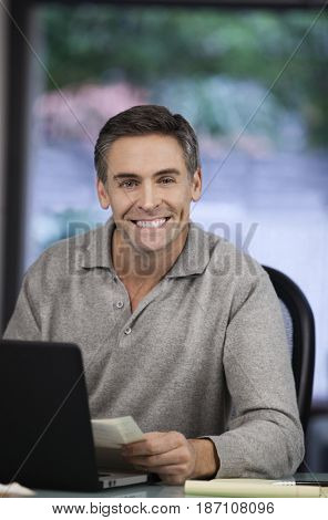 Smiling Caucasian man using laptop