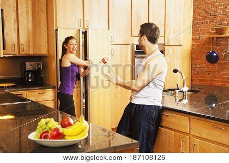 Hispanic woman tossing husband a bottle of water