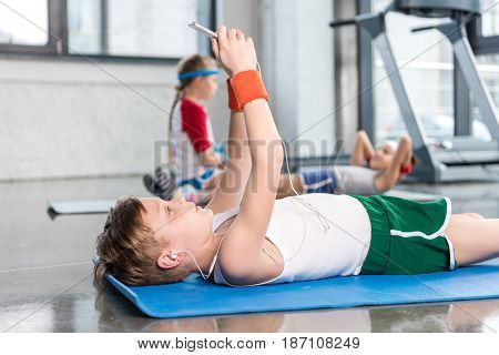 Side View Of Little Boy In Earphones Lying On Yoga Mat And Using Smartphone In Gym, Children Sport S