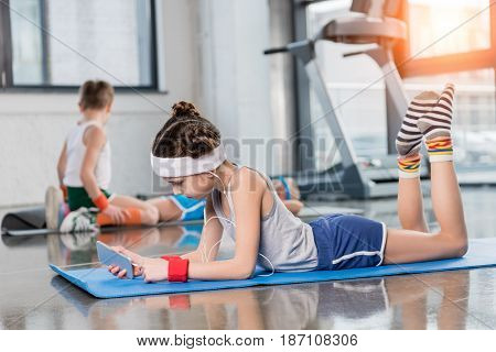 Side view of little girl in earphones lying on yoga mat and using smartphone in gym children sport school concept