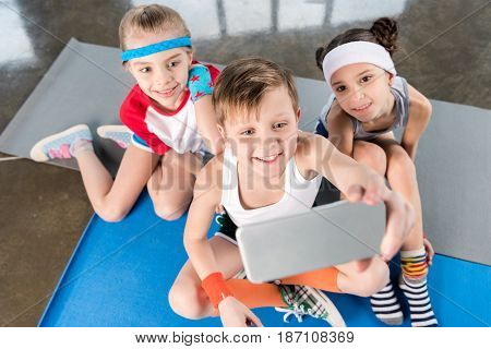 High Angle View Of Cute Sporty Kids Taking Selfie With Smartphone In Gym, Children Sport School Conc