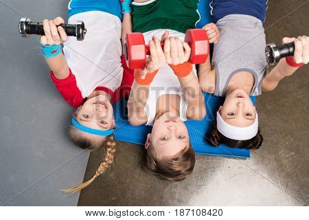 Top View Of Cute Children In Sportswear Lying On Yoga Mat And Exercising With Dumbbells In Gym, Chil