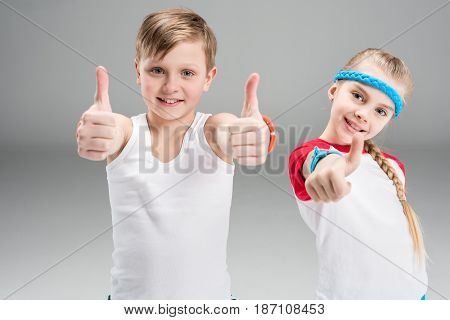 Cute Smiling Boy And Girl In Sportswear Showing Thumbs Up Isolated On Grey, Children Sport Concept