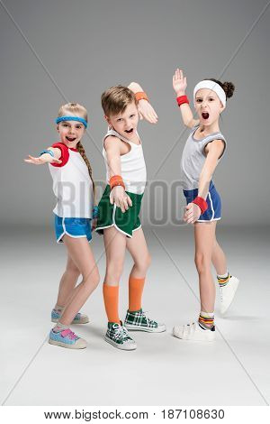 Adorable Sporty Kids In Sportswear Standing Together And Posing Isolated On Grey, Children Sport Con