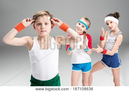 Little Boy In Sportswear Adjusting Eyeglasses And Sporty Girls Standing Behind, Children Sport Conce