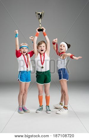 Excited Boy And Girls With Medals And Champion Goblet Isolated On Grey