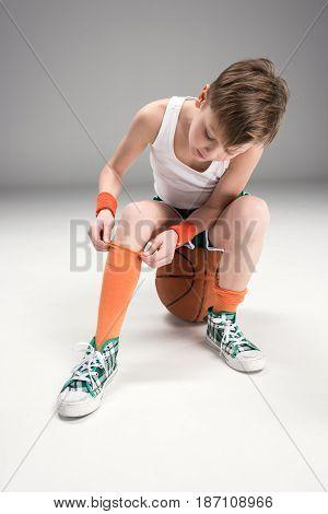 Boy In Sportswear Sitting On Basketball Ball Isolated On Grey