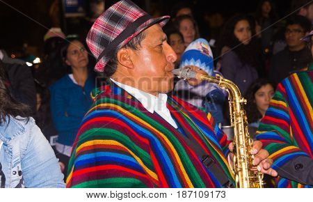 Quito, Ecuador - february 02, 2016: An unidentified man playing his instrument during popular town celebrations wearing a colorful anaco clothes.