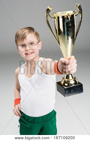 Portrait Of Smiling Boy Showing Champion's Goblet Isolated On Grey