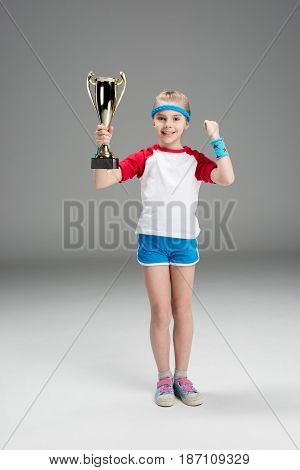 Active Girl Holding Champion's Goblet Isolated On Grey