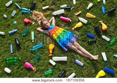 Sad little girl lying on the garbage filled grass - plastic pollution concept