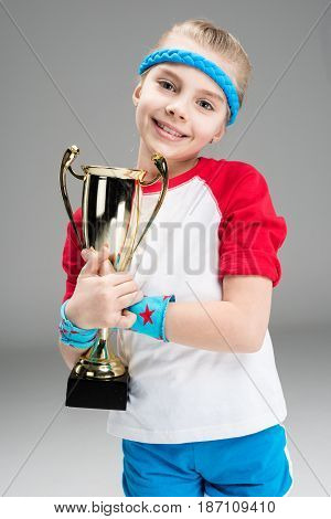 Portrait Of Active Girl Holding Champion's Goblet Isolated On Grey