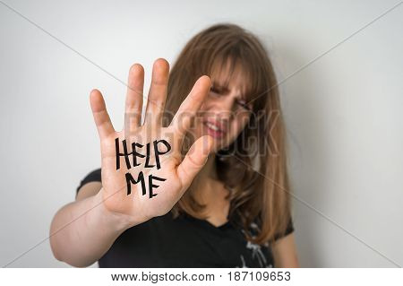 Sad woman is showing hand with message help me - violence concept