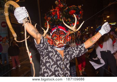 Quito, Ecuador - December 09, 2016: An unidentified man dressed up participating in the Diablada, with a rope in his hand and horns in his head in popular town celebrations.