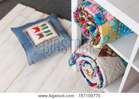 patchwork, sewing and fashion concept - two colorful quilted bedspreads in studio at white shelves with few storage compartments, warehouse of finished products, pillow on floor, top view