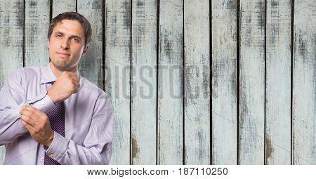 Digital composite of Confident businessman adjusting sleeve against wooden wall