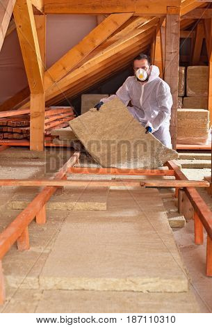 Man places rockwool thermal insulation in layers between wooden scaffolding - working in the attic of a house