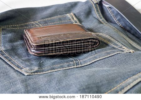 Empty blue old dirty jean with brown wallet on top
