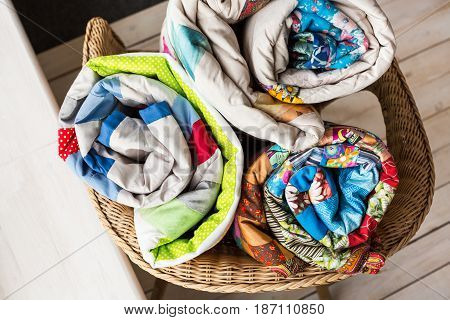 patchwork, quilting and fashion concept - close-up on three colorful quilts rolled into a tube and laid in a wicker chair, warehousing of finished products on a white background