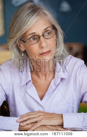 Close up of worried senior woman looking away while sitting at table