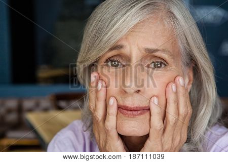 Portrait of worried senior woman in cafe shop