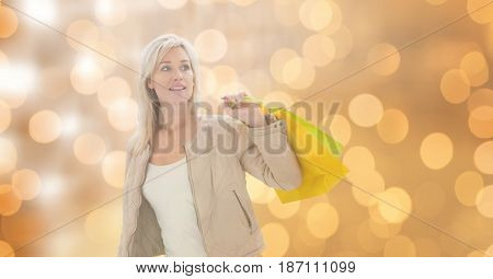 Digital composite of Woman holding shopping bags while looking away