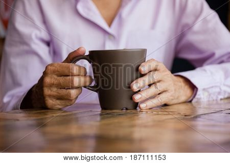 Midsection of woman holding mug while sitting at table in cafe shop