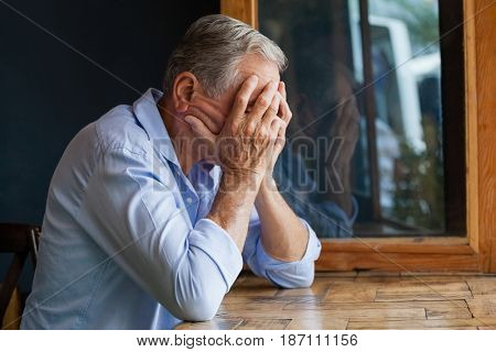 Close up of senior man covering face while sitting at table in cafe