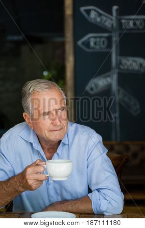 Close up of senior man holding coffee cup at cafe shop