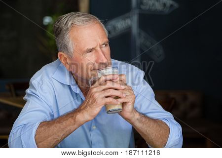 Senior man looking away while holding cold coffee at cafe shop