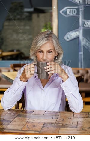 Portrait of senior woman drinking coffee while sitting at table in cafe shop
